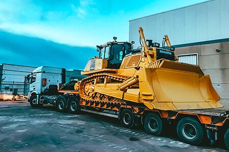 Camión con góndola transportando un bulldozer