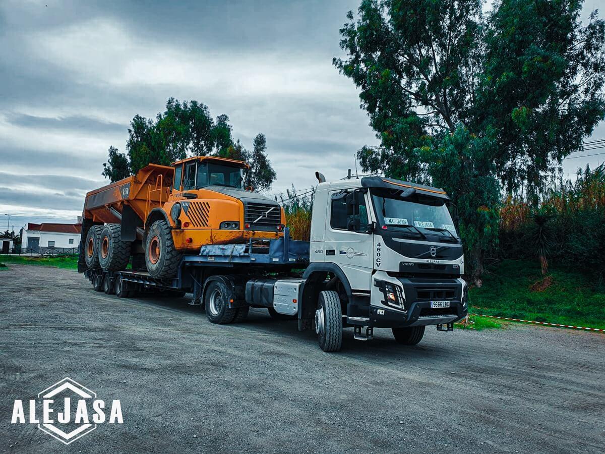 Camión con remolque de góndola transportando maquinaria